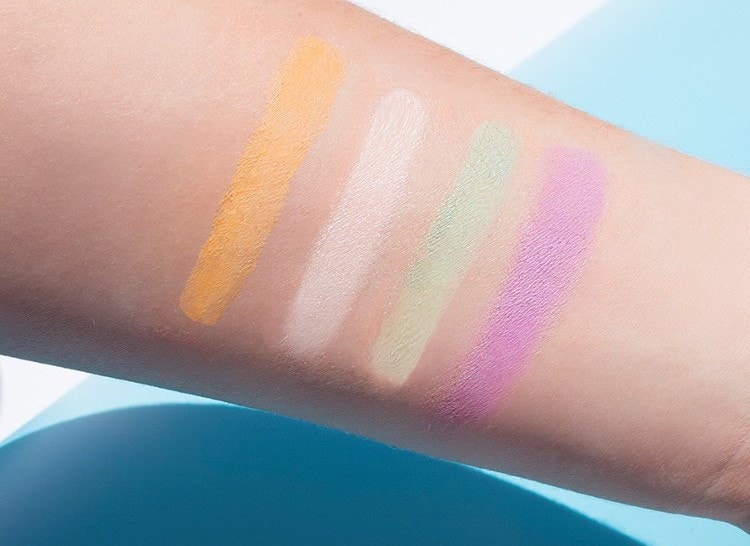 Color correcting concealer colors in yellow, white, green, and purple on arm